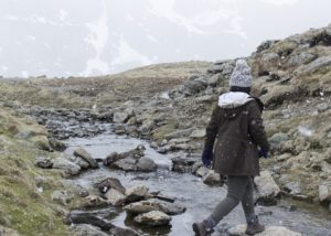 A woman hiking during a light snowfall