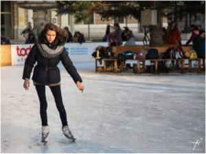 A girl ice skating at an outdoor rink