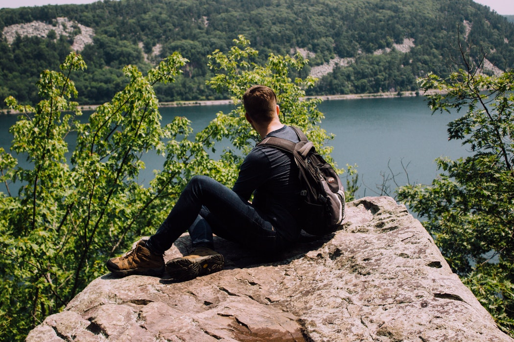 A man sitting on a rock overlooking a lake.